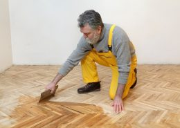 man spreading wood coating on floor