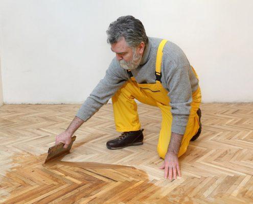 man spreading wood coating on floor